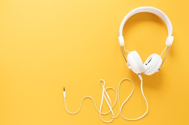 fones de ouvido brancos em um fundo laranja.