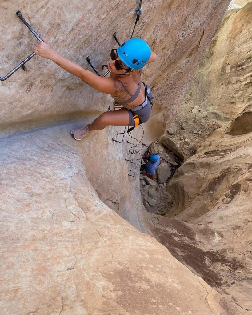 Na foto, a artista Lady Gaga praticando escalada. Ela, que é loira e de pele clara, está bronzeada e protegida com um capacete azul. Usa óculos de sol preto, top e shorts cinza.