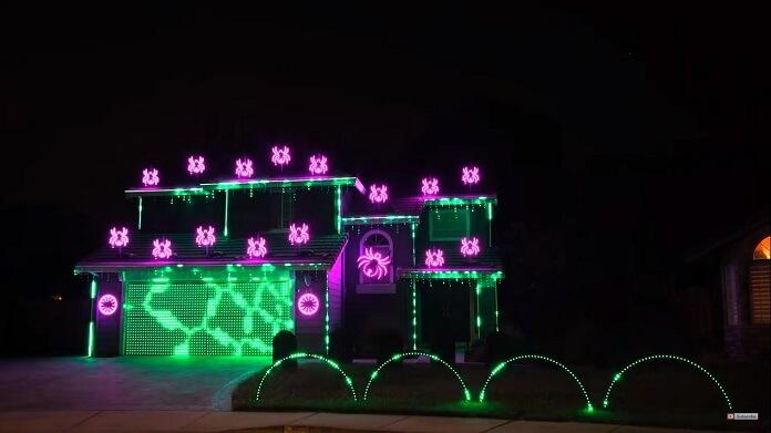 Na imagem, um sobrado fotografado à noite. Ele está decorado com luzes verdes e roxas.