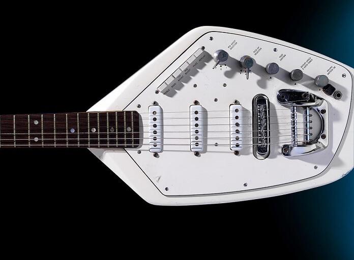 Guitarra toda branca de Ian Curtis em destaque na foto, com um fundo preto.