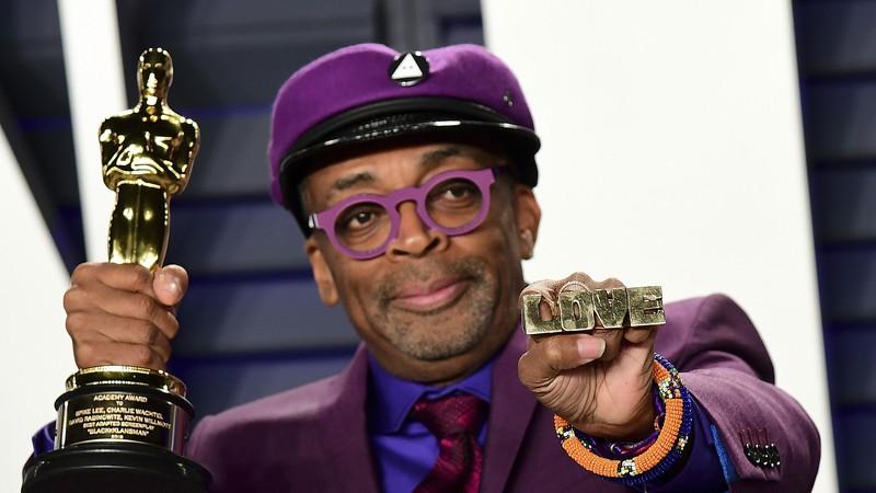 Na foto, Spike Lee, com um terno e boina roxo, além do óculos. Ele está segurando um Oscar e olhando para o lado.