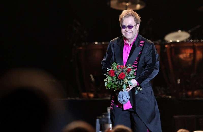 Na imagem, Elton John em pé e sorrindo, segurando um buquê de rosas vermelhas. ele veste um sobretudo preto e uma blusa rosa por baixo. Está de óculos escuros.