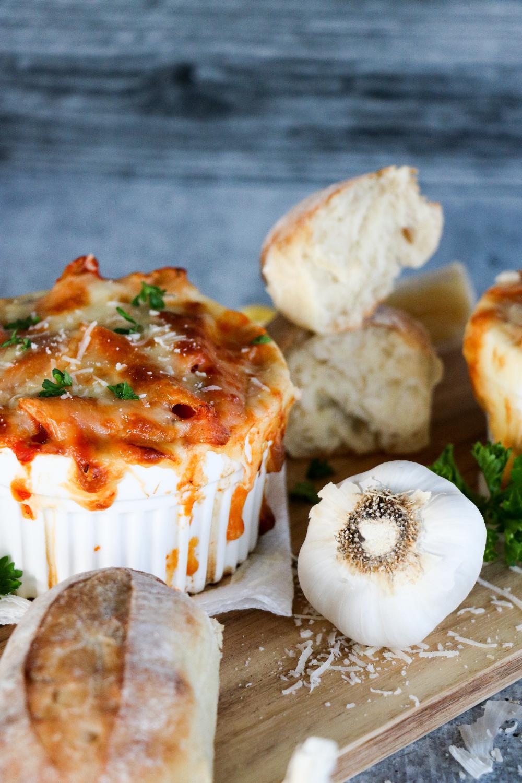 Italian bread, Parmesan cheese, and garlic beside Baked Ziti dish.