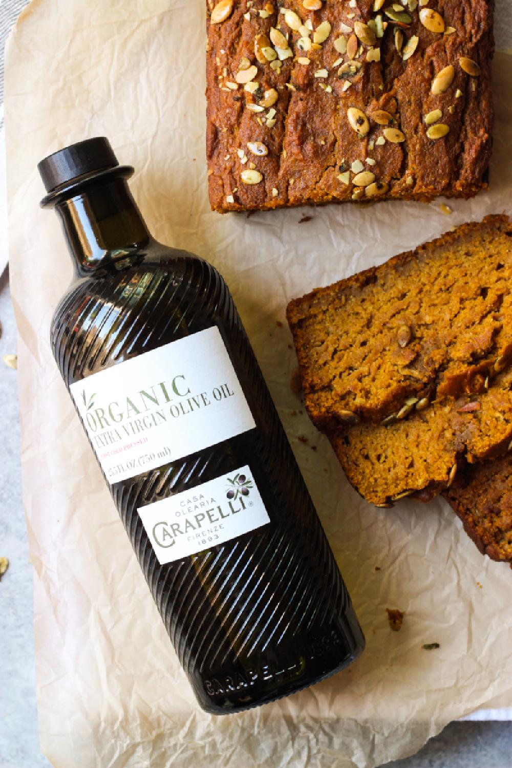 Close up of sliced pumpkin bread and bottle of olive oil