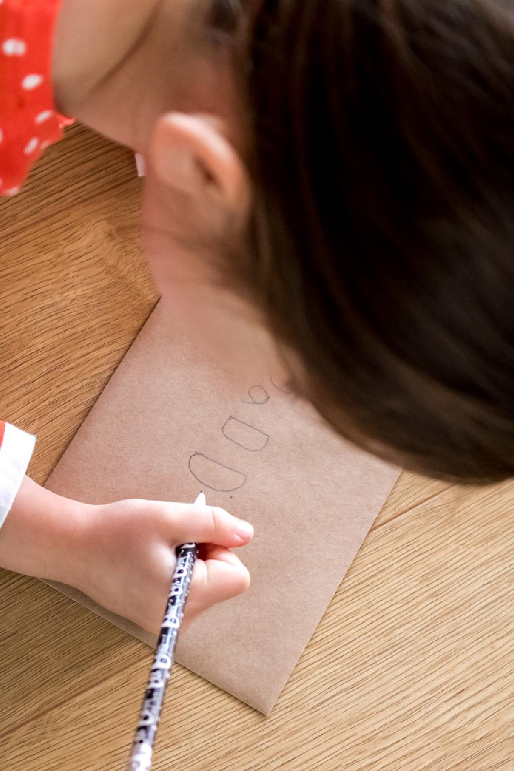 Little girl writing Father's Day Card with Dad and Daughter