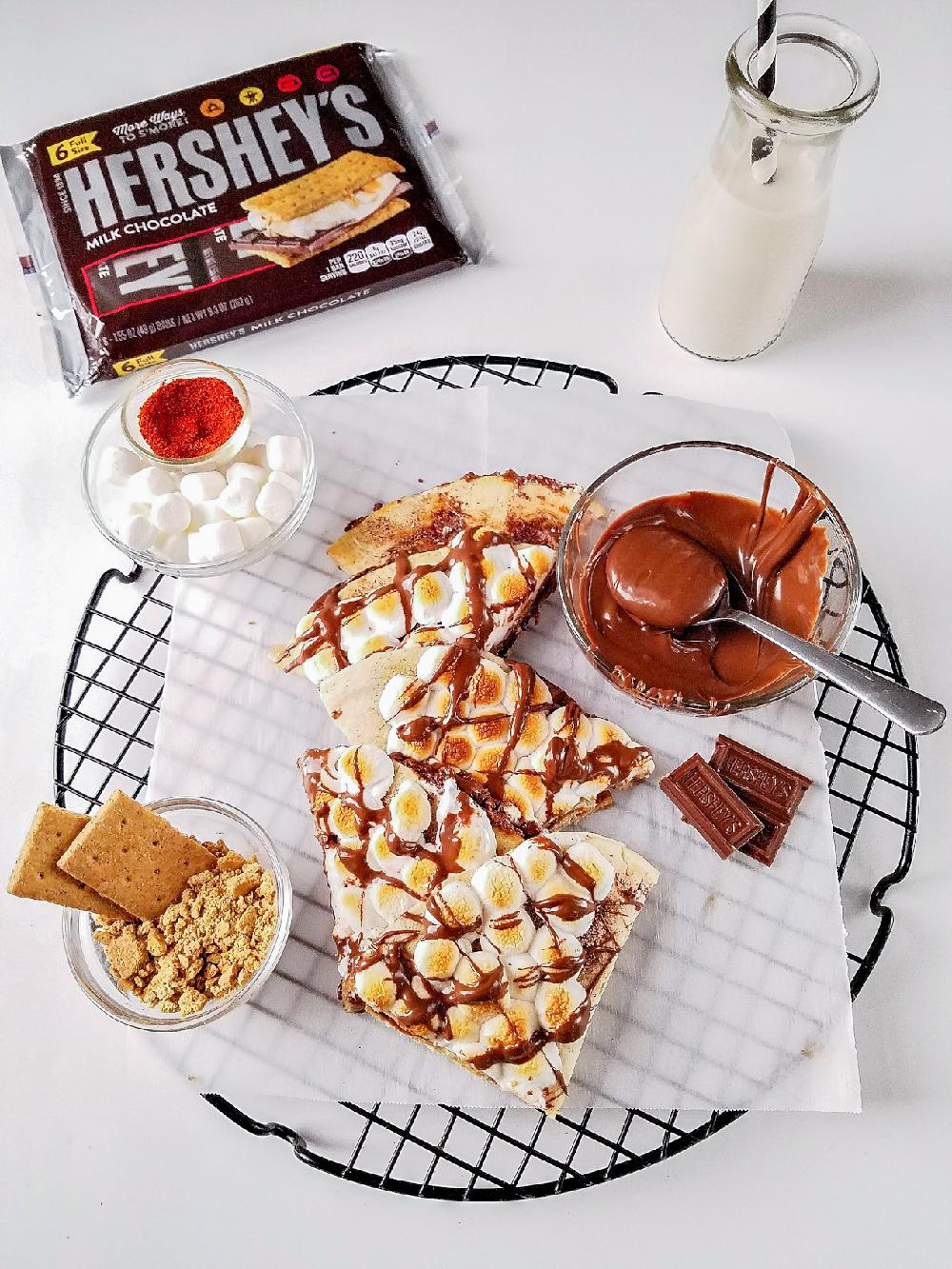 several pieces of s'mores quesadilla on a board with garnishing and milk