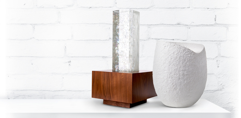 Image of 2 funeral urns for adults. One urn is glass and wood to be displayed at home, second urn is white egg shaped and biodegradable to be buried in a garden.
