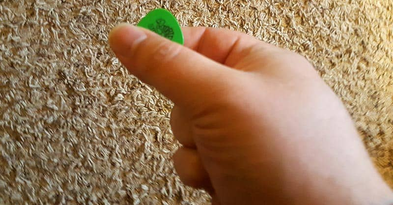 Holding a guitar pick at the tip