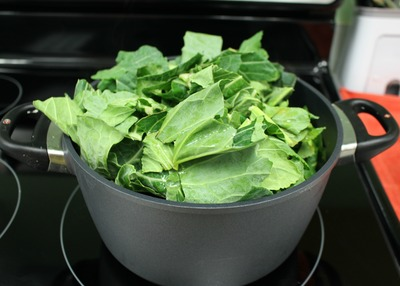 Add the stock, vinegar, seasonings, and some of the greens