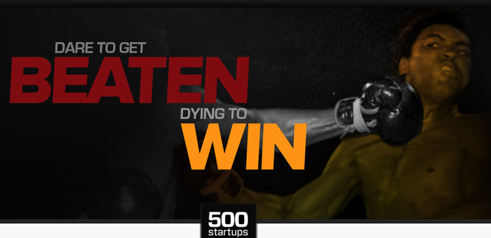A screenshot of the 500 Startups homepage, cropped to show their slogan, which is 'Dare to get beaten, Dying to win.' In the background, a photo of boxer Muhammad Ali being punched in the face by Joe Frazier.