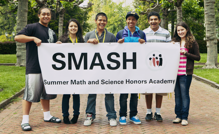 Six LPFI SMASH students are pictured outdoors, on a red brick walkway surrounded on both sides by green grass and trees. They are standing in a row, each helping to hold a large banner print that says SMASH: Summer Math and Science Honors Academy. They are facing the camera and grinning.