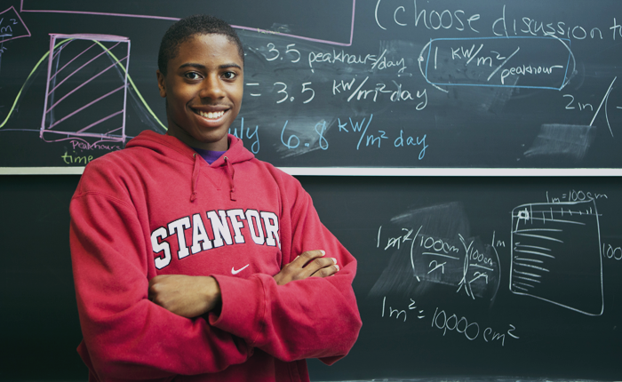A student faces the camera, grinning and arms crossed. They are standing in front of a chalkboard with multi-colored equations, conversions and graphs drawn on it, including 1m^2 = 10,000 cm^2.