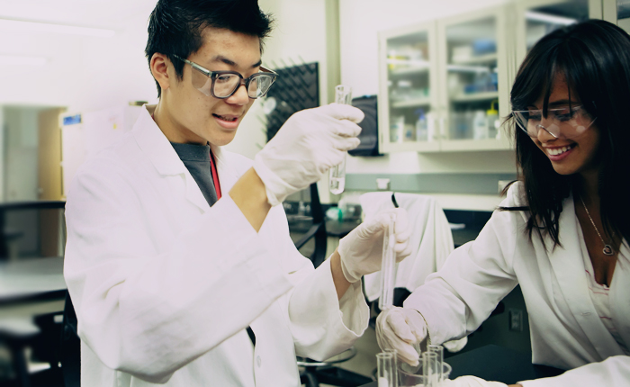 Two students wearing laboratory glasses, lab coats and white gloves examine vials of liquid in a science lab. They are smiling and seem excited. In the background are shelves with laboratory supplies and additional tables.