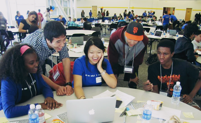 A student team at the Level the Coding Field Hackathon gathers around a laptop, seated at a round table covered with papers, pens and bottles of water. The five students are facing the camera, laughing and looking at something on the laptop screen. In the background are many more round tables and other student teams seated in a similar configuration.