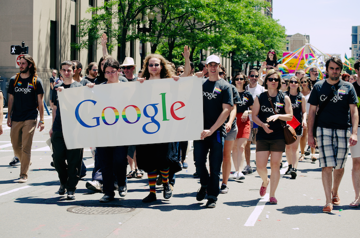 People in Google shirts holding a banner that says 'Google' with rainbow detailing.