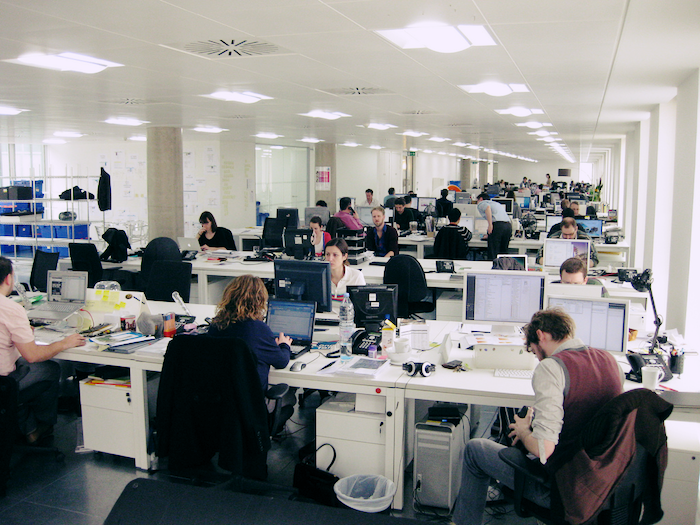 Photo of an office with rows of desks and workers at their computers or talking to colleagues.