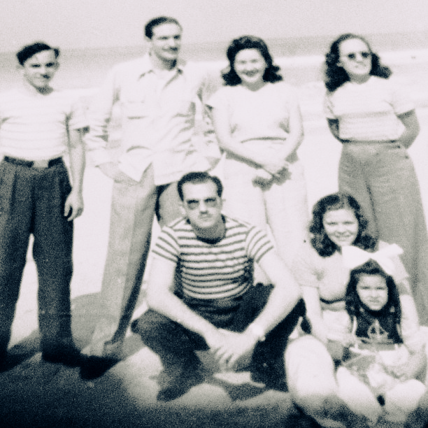 Vintage photograph of a family smiling at the camera.