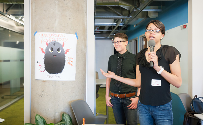 Two hackathon participants, with mics, presenting their work.