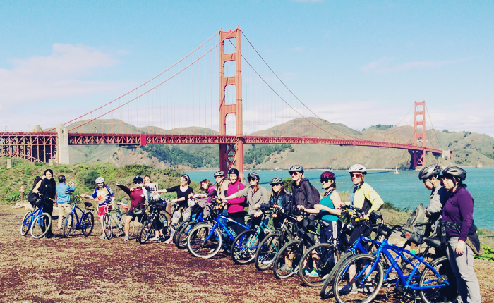 About twenty women wearing bike helmets lined up in front of the Golden Gate Bridge, on a sunny day.