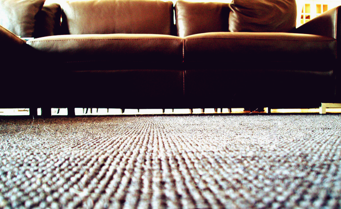 A dark, modern couch, with a nubby rug. No one is in the picture.