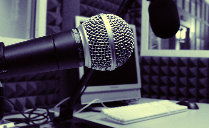 A microphone hanging above a desk, with a computer in the background.