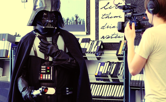 A man in a Darth Vader costume holds a microphone, and a cameraman appears to interview him.