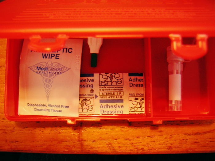 Photo of a blood kit with antiseptic wipe, adhesive dressing and other supplies.