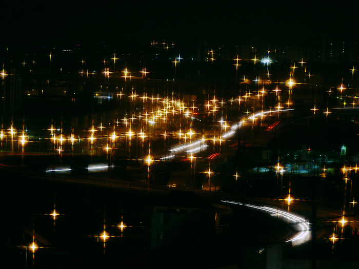 Picture of a roadway at night, street and car lights blurry.