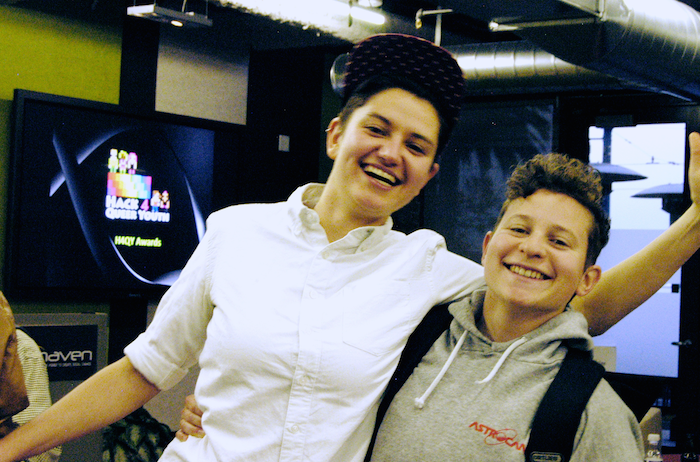 Two winners of a Hack 4 Queer Youth hackathon grin at the camera.
