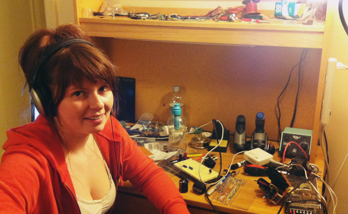 The artist sits at a wooden workbench, facing the camera and wearing a red hoodie. She is also wearing a pair of large headphones and is grinning at the camera. On the workbench behind her are various electrical engineering supplies, including assorted wires, tools, markers, and electrical devices.