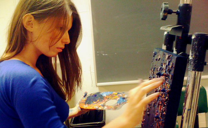 A profile picture of the artist, turned to face an easel and canvas which she is finger-painting with her left hand. The canvas is heavily textured with what looks like small blocks in addition to lots of paint. In her right hand, she holds a palette covered with multi-colored blobs of paint, mainly blues and yellows. Her fingers and wrists are covered with paint. She is concentrating intensely on the painting.