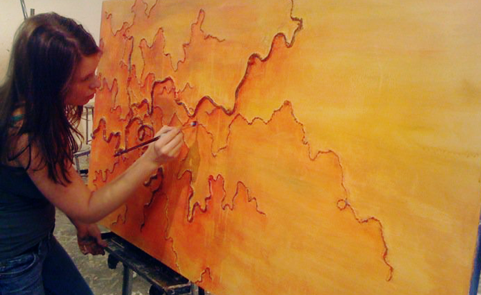The writer painting a very large canvas, filled with vibrant oranges, yellows and reds. The painting itself is abstract but resembles fire, with ridges resembling terrain on a map standing out in darker red. The artist is leaning towards the painting, holding a paintbrush and painting in one such ridge.