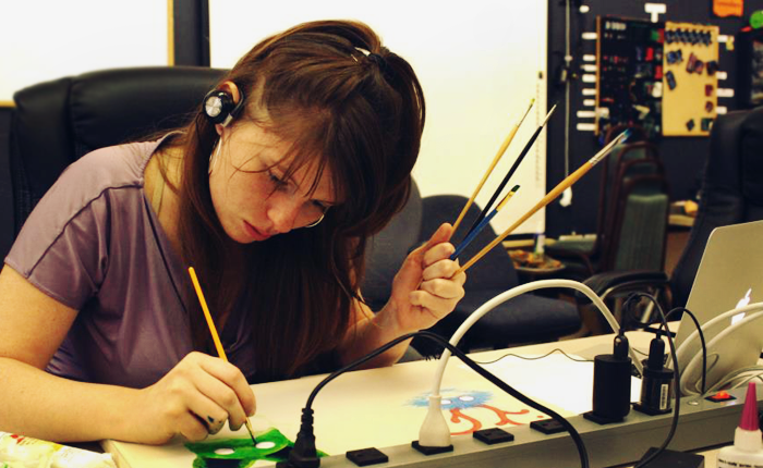 The author is painting a series of animal-like figures on a long sheet of paper. One is a fuzzy blue blob with large, white eyes and elaborate antlers emerging from its head. She is currently painting a green face with mouse-like ears and the same large eyes. She is holding a series of four paint brushes and is wearing headphones as she learns over the painting. Flecks of paint are on her knuckles.