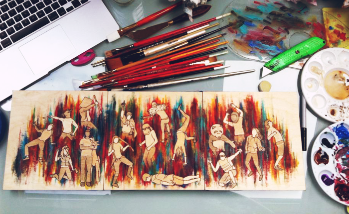 A photograph of the artist's workspace. A laptop touch pad is pictured in the top left, and a number of paint brushes, a clear palette, and a box cutter are also pictured in the top of the photo. A painting of sixteen people dancing - some wearing animal masks, such as panda and horse masks - is in the center of the photo. The people are in various states of dance and merriment, one doing cartwheels, others waving their hands in the air. Behind them are multi-colored, vertical stripes bleeding into each other, giving the painting a feeling of animation and excitement.