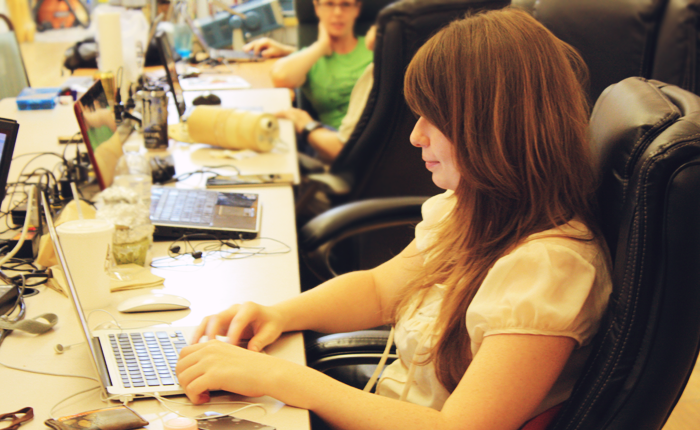 The author is pictured in profile at a long wooden table, with other students in the background but not in focus. She is typing on a laptop, surrounded by a mouse, headphones, paper cups and various wires. She appears to be in a classroom or study environment.
