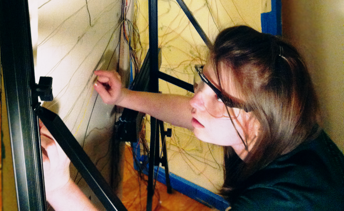 The author is wearing lab glasses and working intently on the wiring within a frame of some sort. There are a number of wires criss-crossing the frame, of various colors. The author is holding down one of the wires stretching from one side of the frame to the other, appearing to be measuring or arranging them within the frame.