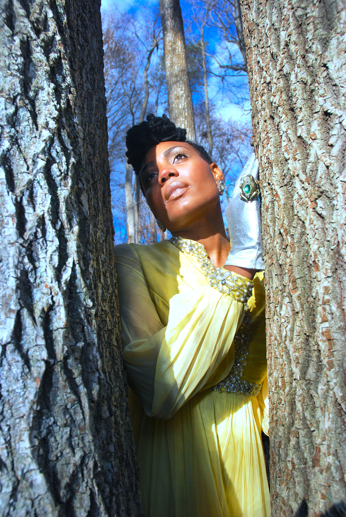 A woman dressed in a beautiful, yellow flowing dress with jewelry at the edges of the fabric and wearing shiny silver-blue gloves with a large ring is pictured between two trees, looking up. A blue sky and more trees are seen behind her.