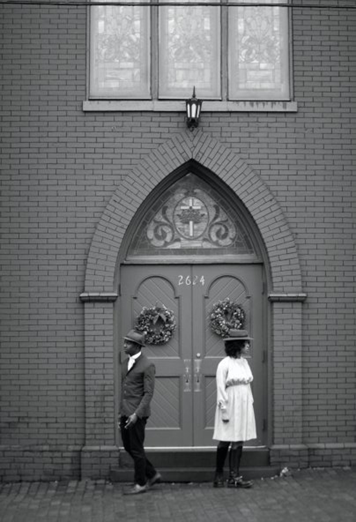 The door of a large brick building is shown, a stained glass window in the archway and wreaths hung above the door handles. A man and a woman stand in front of the door, each wearing hats, backs to each other and facing outward.
