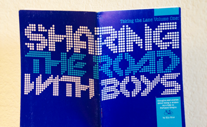 Photograph of Elly Blue's zine titled Sharing the Road with Boys. The title stretches across the front and back of the book, in a font made up of dots.