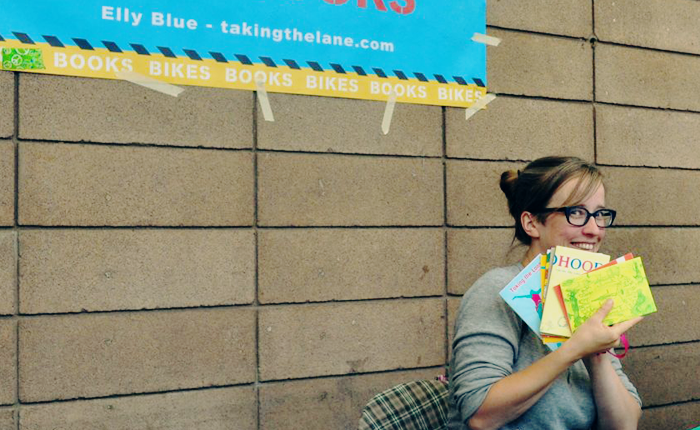 Elly Blue, the author of this piece, posing with a handful of issues of Taking the Lane, her zine about bicycling and feminism. Blue is grinning. In the background a sign for her publishing company is taped to a cinderblock wall.