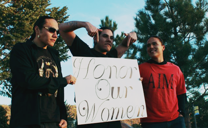 Three men wearing jeans and t-shirts stand outside, surrounded by trees and a very blue sky. There are some houses barely visible in the background. They are holding a sign up on posterboard that says Honor Our Women in cursive. One is lifting his arms and pointing down to the photo as the other two hold the posterboard on either side of him.