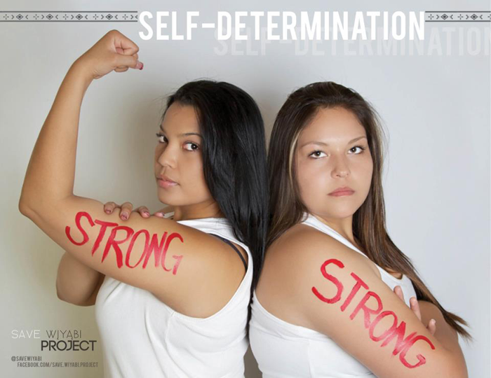A poster for the Save Wiyabi Project. It reads Self-Determination at the top of the image. Two Indigenous women stand back-to-back, facing the camera. One has her arms crossed, and the other is raising her arm with her fist clenched, her other hand grasping her bicep. Both of their biceps have the word Strong painted on them in red ink.
