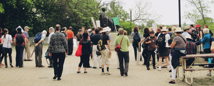 A crowd of 40 or so people gathers around the statue of Arthur Doughty, most facing the statue and gathered in a semi-circle. Some hold signs, but the words are facing away from the camera. A few sit on a picnic table situated near the the statue.