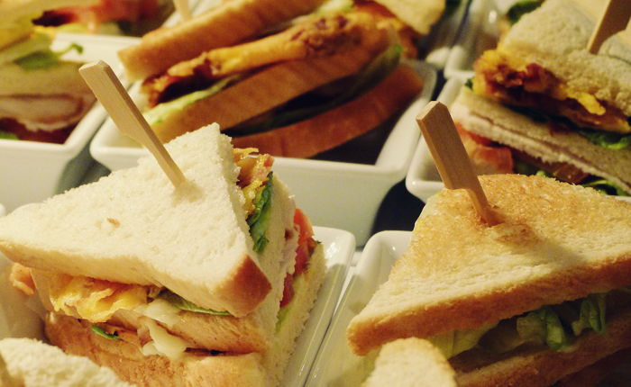 Photo of club sandwiches, cut into tiny triangles.
