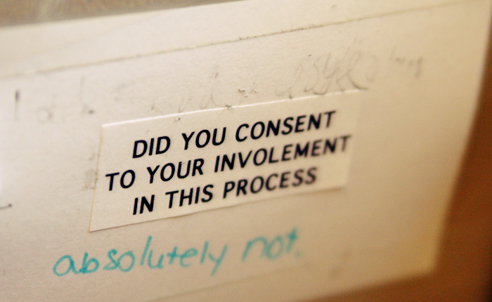 A printed out sign that appears to be taped up in a public bathroom says 'Did you consent to your involvement in this process' - underneath, someone has scrawled 'Absolutely not' in green marker.