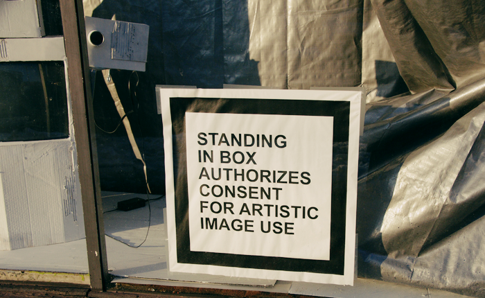 A square sign with a thick black border which reads: 'Standing in box authorizes consent for artistic image use.' The sign is taped in a window that has something that appears to be a camera covered in cardboard. The rest of the window is draped in a tarp.