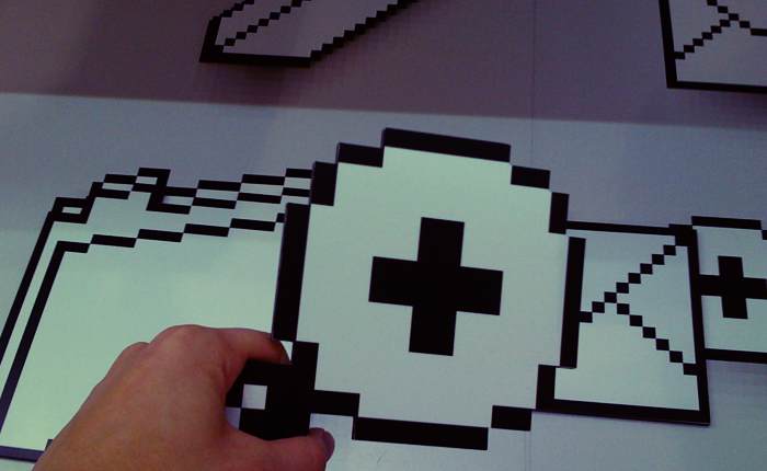 A hand holds a large cardboard cutout of a pixelated magnifying glass of the type used to signify zoom on most software. In the background, large cardboard cutouts of pixelated erasers, folders, and other computer icons.