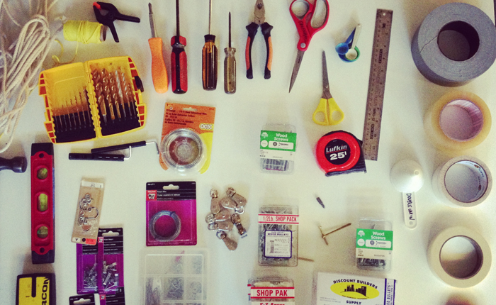 A close-up of hardware supplies, including four screwdrivers, a balance device, drill bits, wood screws and some coiled rope and thread.