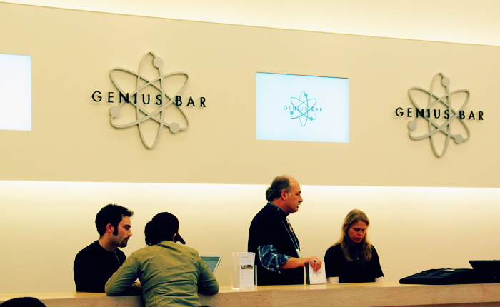 An example of the type of retail technician work Howard references, Apple Genius Bar, shown with three workers standing behind a counter.