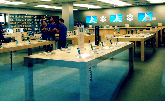 Three workers, in blue shirts and name badges, talking to one another in an empty Apple store.